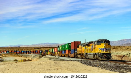 Palm Springs,USA  - January, 2018 : Cargo train passing by the desert in Palm Springs ,California, USA. A railroad car is a vehicle used for the carrying of cargo on a railway.