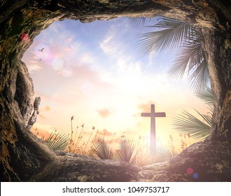 Palm Sunday concept: Silhouette cross and empty tombstone with palm leaves over meadow sunset background