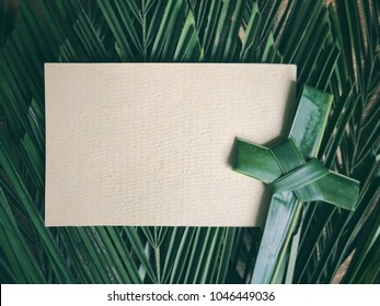 Palm Sunday concept. White blank paper and a cross made of palm leaf. With arranged green palm leaves as background.