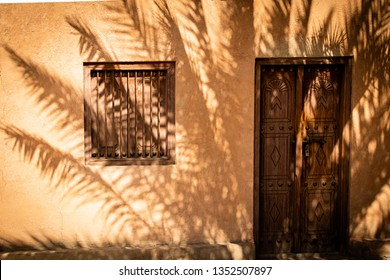A palm is throwing its beautiful shade on the front of a house in UAE, Al Ain.