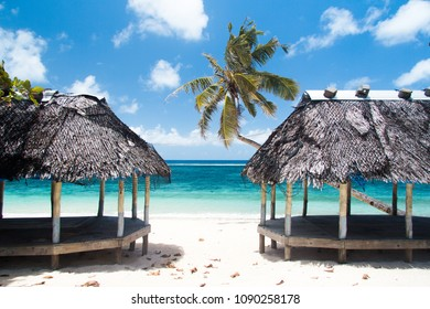 palm tree and beach fales on sandy beach in tropical island of Samoa with clean blue water