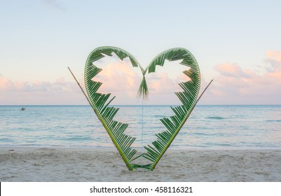 Palm tree branches are tied into the shape of a heart, on a quiet beach on the island of Koh Pha Ngan, Thailand .