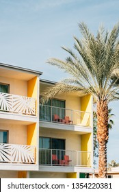 Palm tree and colorful hotel with balconies in Palm Springs, California