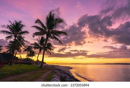 Palm tree silhouette against a beautiful sunset on the Fijian coast