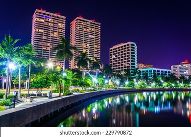 Palm trees along the Intracoastal Waterway and the skyline at night in West Palm Beach, Florida.