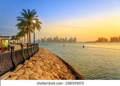 Palm trees along marina walkway in Porto Arabia at the Pearl-Qatar, Doha, with skyscrapers of West Bay skyline at sunset sky. Scenic sunset landscape of Persian Gulf in Middle East.