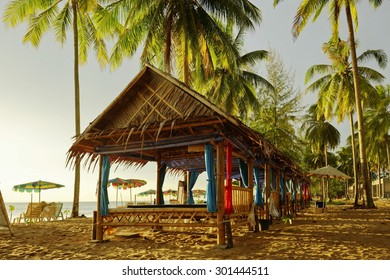 Palm trees and colorful beach huts in Thailand
