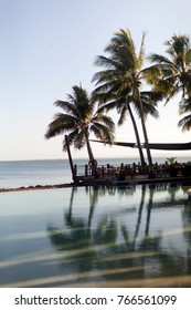 Palm trees during sunset reflected in a hotel pool in a tropical spa in Fiji