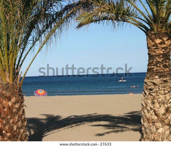 Palm trees framing a shot of a parasol on a spanish beach