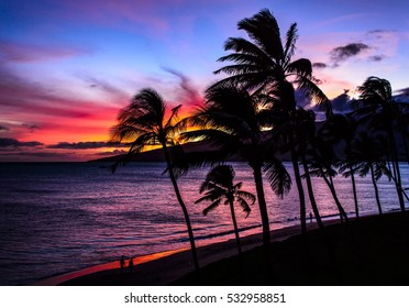 Palm trees and the ocean against a beautiful Maui sunset on Sugar Beach Kihei Hawaii