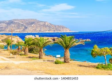 Palm trees on coastal promenade along beautiful sea coast of Karpathos island near Ammopi village, Greece
