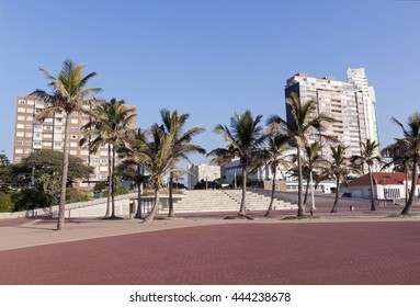 Palm trees on empty promenade and concrete terrace against Golden Mile beach front city skyline in Durban South Africa