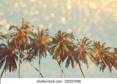 Palm trees on tropical shore with golden party glamour bokeh overlay, double exposure effect stylized