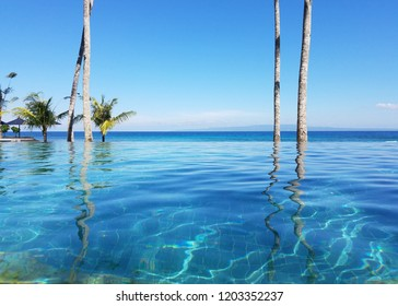 Palm trees reflected in an infinity pool overlooking the Indian Ocean in a resort on Candidasa beach in Bali, Indonesia