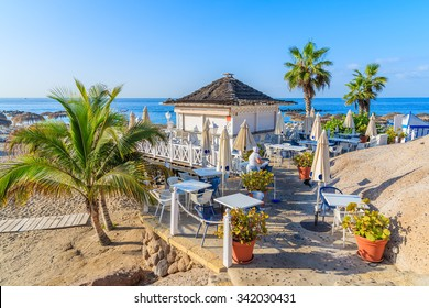 Palm trees and restaurant building on El Duque beach in Costa Adeje town, Tenerife, Canary Islands, Spain