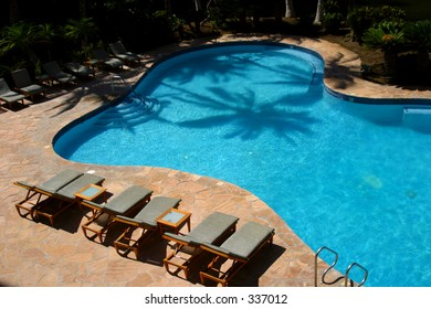 A palm tree's shadow is cast  on the water of a swimming pool at a resort hotel on the Big Island of Hawaii.