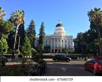 Palm trees swaying and cars driving by the California State Capitol building in Sacramento, CA