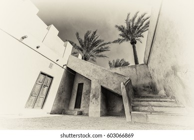 Palm trees tower above an angled staircase over carved wooden doors in this sepia wide-angle ground level view of a restored traditional house in the Arabian Gulf.