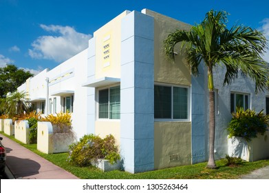 Palm trees and tropical plants decorate the exterior of a simple single story Art Deco building under bright blue sky in South Beach, Miami, Florida, USA