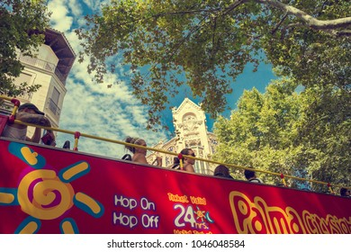 PALMA DE MAJORCA, SPAIN - AUGUST 26, 2017: Tourists go to the red tour bus on the street in the centre of Palma in Majorca in Spain on a summer day