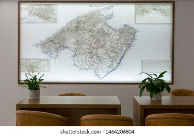 PALMA DE MALLORCA, BALEARIC ISLANDS, SPAIN - JUNE, 2019: Detailed illuminated island map in the hotel lobby with tables and chairs