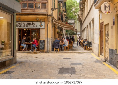 Palma de Mallorca, Spain; april 23 2021: Restaurant terrace full of diners at noon in the historic center of Palma de Mallorca. Use of face mask and safety distance due to the Coronavirus pandemic