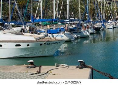 PALMA DE MALLORCA, SPAIN - APRIL 19, 2015: Mediterranean maritime scene with yachts, palm trees and moorings on April 19, 2015 in Palma de Mallorca, Balearic islands, Spain.