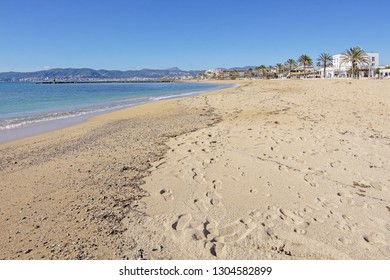 PALMA DE MALLORCA, SPAIN - FEBRUARY 4, 2019: Empty sand beach in Ciudad Jardin and promenade with blue sky on a sunny day on February 4, 2019 i Palma de Mallorca, Spain.