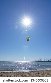 PALMA DE MALLORCA, SPAIN - MARCH 17, 2019: Kitesurfer flying high against blue sky with sun and flares ocean horizon on a sunny and windy day on March 17, 2019 in Palma de Mallorca, Spain