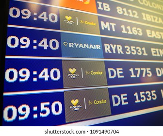 PALMA DE MALLORCA, SPAIN - MAY 8, 2018: Departure hours of airport information board with mutiple airlines hours departure gates and insignia for the boarding gate light flare sunlight