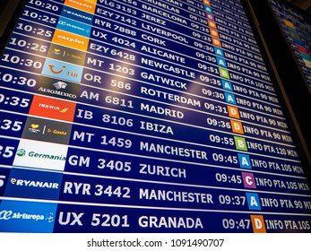 PALMA DE MALLORCA, SPAIN - MAY 8, 2018: View from below of large details of a typical airport information board with mutiple airlines and cities hours departure gates and insignia for the boarding