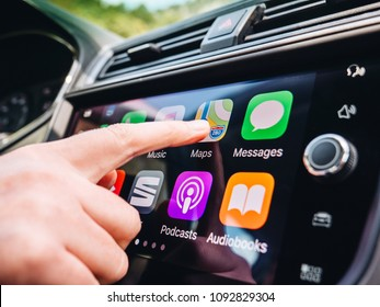 PALMA DE MALLORCA, SPAIN - MAY 10, 2018: Woman pressing Apple Maps button on the Apple CarPlay main screen in modern car dashboard during driving on Spanish holiday highway
