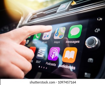 PALMA DE MALLORCA, SPAIN - MAY 10, 2018: Woman pressing Apple Maps button on the Apple CarPlay main screen in modern car dashboard during driving on Spanish holiday highway - large digital display