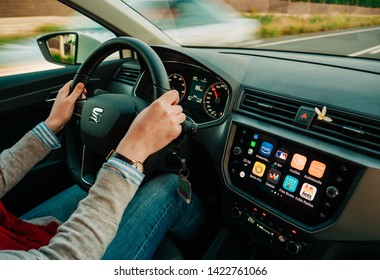 Palma de Mallorca, Spain - May 8, 2018: Young adult woman driving fast on spanish Highway at dusk a Seat car using Apple Car iOS with multiple applications such as Amazon music, Audible, Deezer, Maps