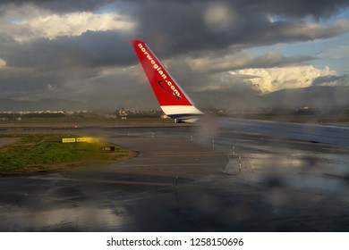 PALMA DE MALLORCA, SPAIN - NOVEMBER 9, 2018: Rain and sunshine abstract effects through window with red Norwegian airplane wing on a sunny winter morning  on Son Sant Juan airport on November 9, 2018