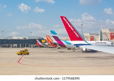 PALMA DE MALLORCA, SPAIN - SEPTEMBER 6, 2018: Airplane tail fins from Norwegian, Eurowings, Easyjet on the tarmac outside gates on a sunny day on September 6, 2018 in Mallorca, Spain.