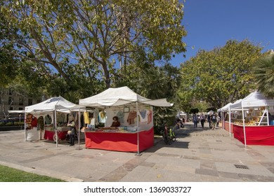 PALMA, MALLORCA, SPAIN - APRIL 9, 2019: Vendor huts displaying craft with Almudaina castle in the background on a sunny day on April 9, 2019 in Palma, Mallorca, Spain.