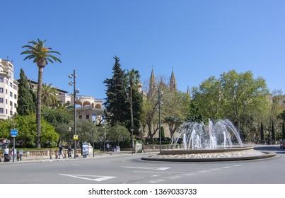 PALMA, MALLORCA, SPAIN - APRIL 9, 2019: Fountain and roundabout on Plaza de la Reina in the city on a sunny day in Palma, Mallorca, Spain.