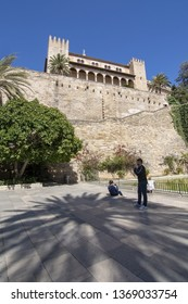 PALMA, MALLORCA, SPAIN - APRIL 9, 2019: Tourists in front of Almudaina castle on a sunny day on April 9, 2019 in Palma, Mallorca, Spain.
