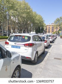 PALMA, MALLORCA, SPAIN - APRIL 9, 2019: Taxi cars waiting in a row in central city on a sunny day on April 9, 2019 in Palma, Mallorca, Spain.
