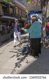 PALMA, MALLORCA, SPAIN - APRIL 9, 2019: Female violinist entertains the sidewalk on Plaza de la Reina in the city on a sunny day on April 9, 2019 in Palma, Mallorca, Spain.