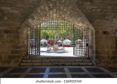 PALMA, MALLORCA, SPAIN - APRIL 9, 2019: Old stone portal with view to tourist bus on a sunny day on April 9, 2019 in Palma, Mallorca, Spain.