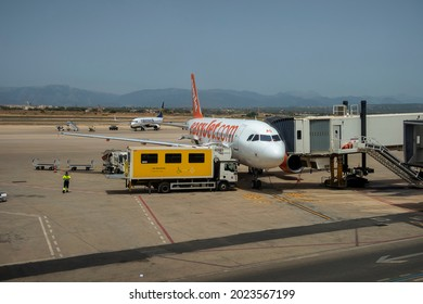 Palma, Mallorca, Spain - July 2021: An Easyjet aircraft connected to an airbridge at Palma de Mallorca airport in Spain