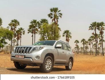 Palmarin, Senegal -27 June 2020: Toyota Prado 4X4 in front of the palm trees. Palmarin is a coastal village in Senegal, located in Sine-Saloum near Sangomar Point between Joal-Fadiouth and Djifer
