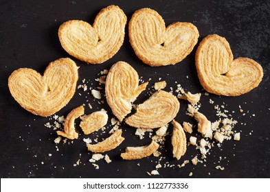 Palmiers, whole and broken puff pastry cookie on old black metal background, top view