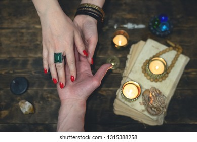 Palmistry concept. Fortune teller reading future on the hand on a magic table background. Future reading concept.