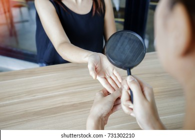 Palmistry fortune teller using magnify glass on woman hand to read the line.