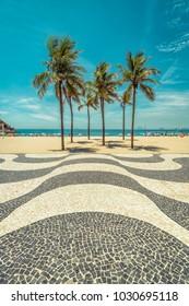 Palms on Copacabana Beach with famous mosaic boardwalk in Rio de Janeiro, Brazil