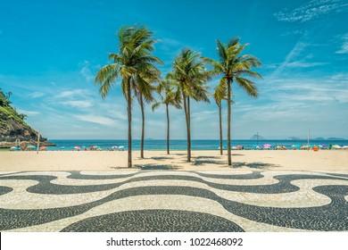 Palms on Copacabana Beach and landmark mosaic in Rio de Janeiro, Brazil. Sunny day with blue sky