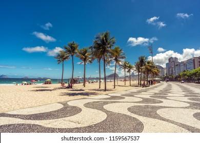Palms on Copacabana Beach and landmark mosaic sidewalk in Rio de Janeiro, Brazil.